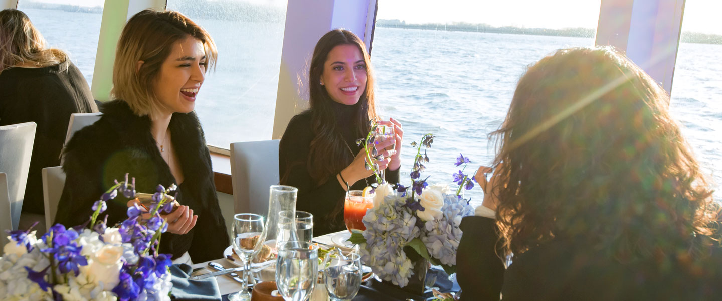 group of women dining on world yacht for a corporate outing